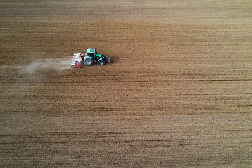 Planting「Tractor with seed drill seeding crops at field, aerial view」:スマホ壁紙(4)