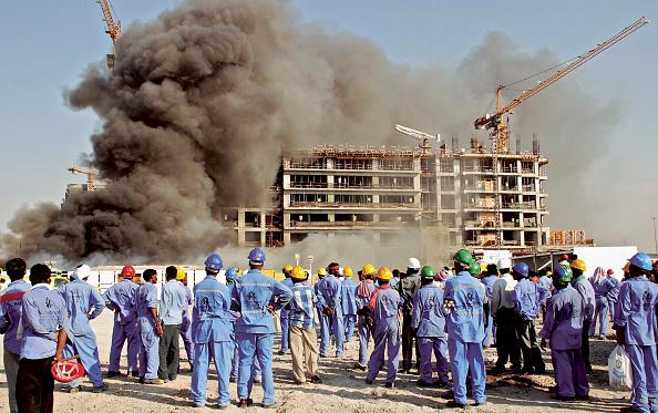 Insurance「Al Mumzar industrial area. Labourers watch their building under construction hit by fire, Dubai, United Arab Emirates, October 22, 2006.」:写真・画像(13)[壁紙.com]