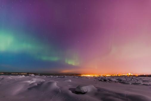 アラスカ「The Northern Lights Shine Above The Anchorage City Skyline In This Nighttime View From The Tony Knowles Coastal Trail In Winter」:スマホ壁紙(6)
