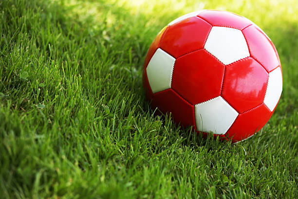 Red soccer ball in grass:スマホ壁紙(壁紙.com)