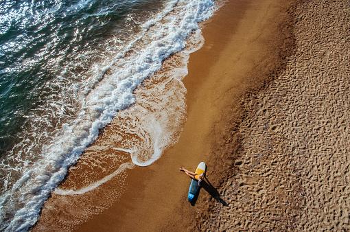 サーフィン「Aerial view of a surfer girl resting on a beach」:スマホ壁紙(19)
