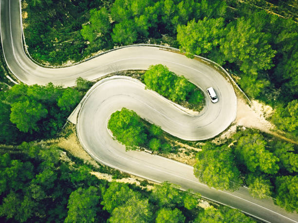 Aerial view of a two lane winding road in a forest with a white car.:スマホ壁紙(壁紙.com)