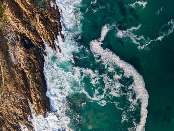 Aerial view of sea waves crashing against rocky coast:スマホ壁紙(壁紙.com)