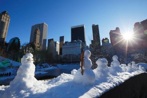 雪だるま「Sunset illuminates snowman from behind skyscrapers」:スマホ壁紙(15)