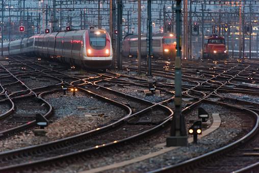 Railroad Junction「Commuter train approaching busy railway track field at twilight」:スマホ壁紙(4)