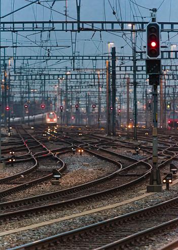 Electricity Pylon「Commuter train approaching busy railway track field at twilight」:スマホ壁紙(6)
