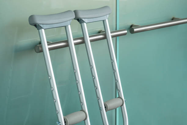 Pair of metal crutches leaning against a modern steel handle on a glass door.:スマホ壁紙(壁紙.com)