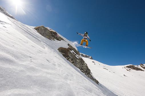 スノーボード「Man with snowboard jumping in midair while riding off piste」:スマホ壁紙(11)