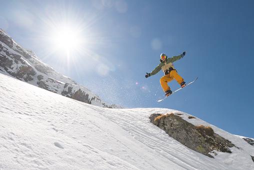 スノーボード「Man with snowboard jumping in midair on steep slope」:スマホ壁紙(2)