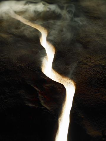 Lava「Smoke and light coming through crack in lava rock, elevated view」:スマホ壁紙(6)