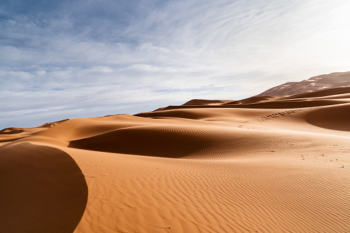 Arid Climate「Huge, sandy orange dunes and cloudy sky in the desert of Merzouga, Morocco.」:スマホ壁紙(11)