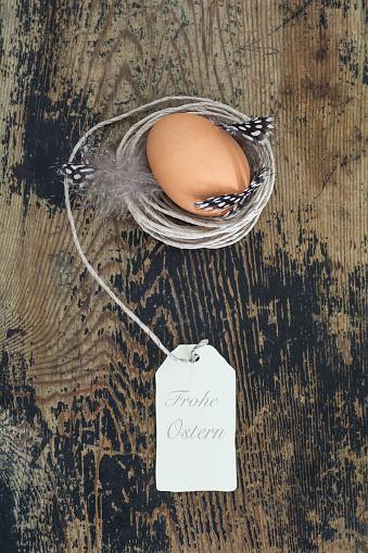 イースター「Brown egg in nest built of cord on wood」:スマホ壁紙(16)