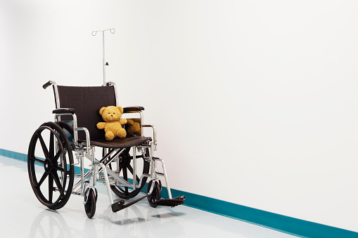 Unrecognizable Person「Wheelchair with teddy bear in hospital corridor」:スマホ壁紙(0)