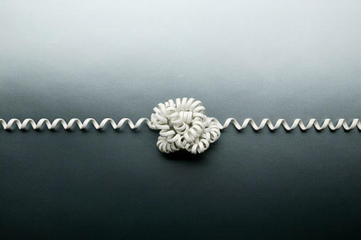 Problems「Coiled telephone cord tied in a knot on gray background」:スマホ壁紙(3)