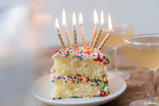 Drinking「Candles burning on slice of cake with sprinkles near champagne」:スマホ壁紙(4)