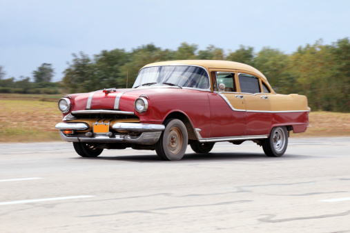 Unrecognizable Person「Old classic car drives by Cuban highway」:スマホ壁紙(7)