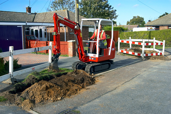 Earth Mover「Utility company excavating the pavement with mini digger」:写真・画像(9)[壁紙.com]