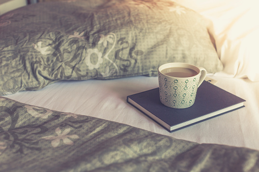 趣味・暮らし「Book and cup of white coffee on a bed」:スマホ壁紙(4)