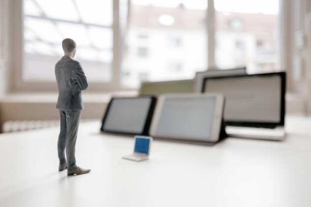 Businessman figurine standing on desk, facing mobile devices:スマホ壁紙(壁紙.com)