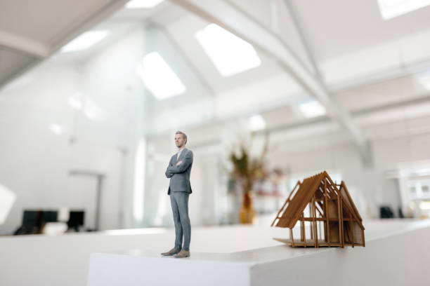 Businessman figurine standing on desk next to architectural model:スマホ壁紙(壁紙.com)