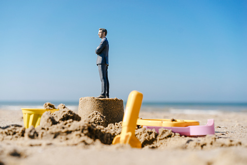Sand Pail and Shovel「Businessman figurine standing on sand with toys around」:スマホ壁紙(5)