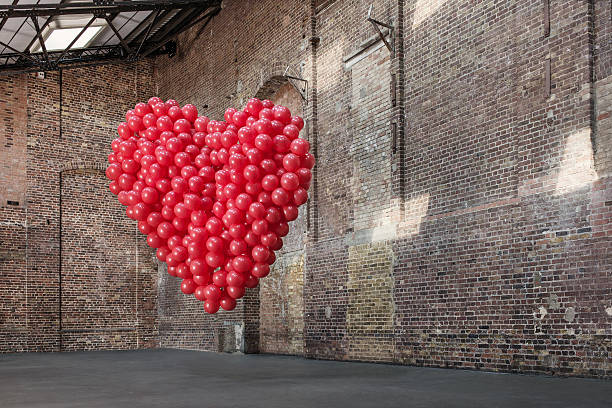 Empty warehouse with red heart made of balloons:スマホ壁紙(壁紙.com)