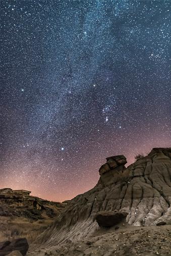 満ちていく月「Orion and the winter stars over the badlands of Dinosaur Provincial Park, Canada.」:スマホ壁紙(15)