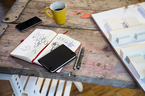 Pen「Notebook, smartphone, architectural model and coffee cup in modern informal office」:スマホ壁紙(11)