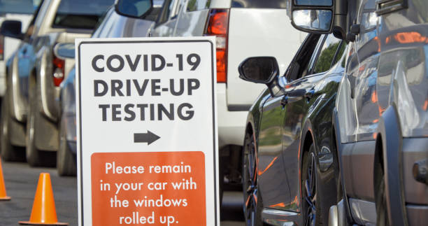 """A """"COVID-19 Drive-Up Testing"""" Sign Sits in the Foreground While Cars and Other Vehicles Wait in a Drive-Up (Drive Through) COVID-19 (Coronavirus) Testing Line Outside a Medical Clinic/Hospital Outdoors (Second Wave) in the Background:スマホ壁紙(壁紙.com)"""
