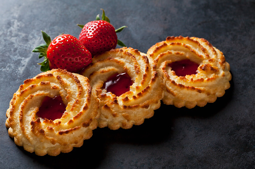 Biscuit「Three ox-eye cookies and two strawberries on dark metal」:スマホ壁紙(10)