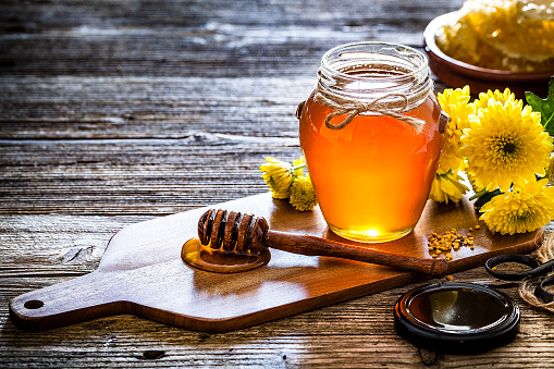 Chemical「Honey jar with honey dipper shot on rustic wooden table」:スマホ壁紙(1)