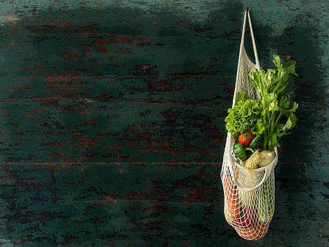 Celery「Market fresh salad vegetables hanging in a reusable string cotton bag, on an old wood turquoise colored wall background.」:スマホ壁紙(8)