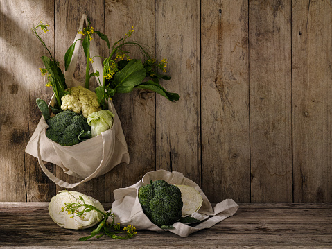 Cauliflower「Market fresh green leafy vegetables in a cotton reusable shopping bag hanging from an old hook on an old weathered wooden panel wall, with more vegetables under the bag on a wooden table.」:スマホ壁紙(19)
