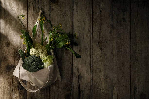Market fresh green leafy vegetables in a cotton reusable shopping bag hanging from an old hook on an old weathered wooden panel wall.:スマホ壁紙(壁紙.com)