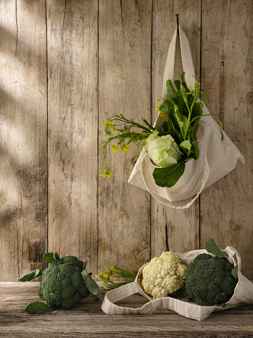 Cauliflower「Market fresh green leafy vegetables in a cotton reusable shopping bag hanging from an old hook on an old weathered wooden panel wall, with more vegetables under the bag on a wooden table.」:スマホ壁紙(10)