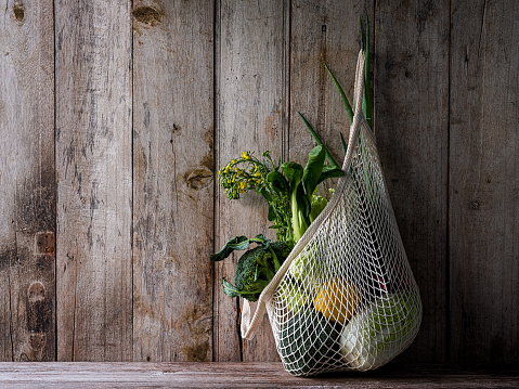 Wood Paneling「Market fresh vegetables hanging in a reusable string cotton bag, on an old wood board wall background.」:スマホ壁紙(1)