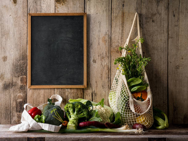 Market fresh vegetables hanging in a reusable cotton bag next to a blackboard, on an old wooden board wall background, above an old wooden table with other vegetables.:スマホ壁紙(壁紙.com)