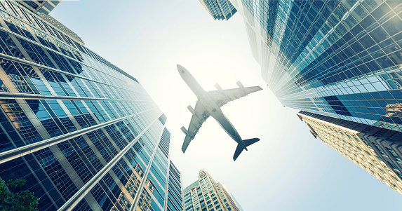 Commercial Airplane「Low angle view of buildings with plane flying overhead」:スマホ壁紙(11)