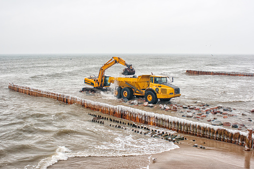 Shallow「Excavator truck loading stones into a truck on the beach, Baltic Sea, Kaliningrad, Russian Federation」:スマホ壁紙(18)