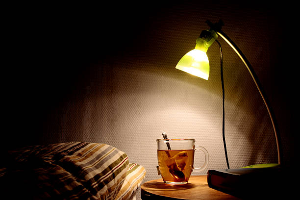 Bright bedside lamp with a clear cup of tea next to the bed:スマホ壁紙(壁紙.com)