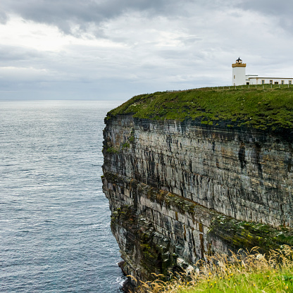 スコットランド文化「Duncansby Head Lighthouse on the edge of a cliff on the coast under a cloudy sky」:スマホ壁紙(6)