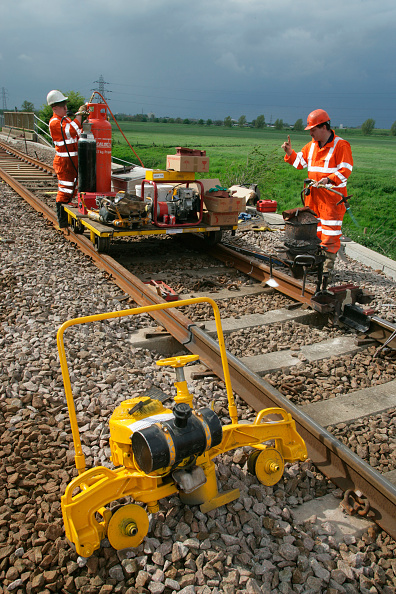Grinder - Industrial Equipment「Trackworkers prepair to carry out thermit welding on newly laid track whith a rail grinding machine in the foreground. Peterborough. May 2005」:写真・画像(11)[壁紙.com]
