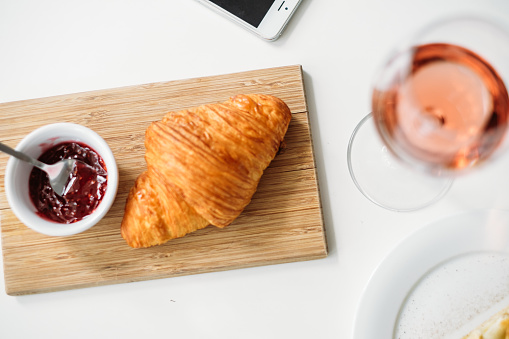 Liquor「Overhead view of a croissant with jam and a glass of rose wine」:スマホ壁紙(13)