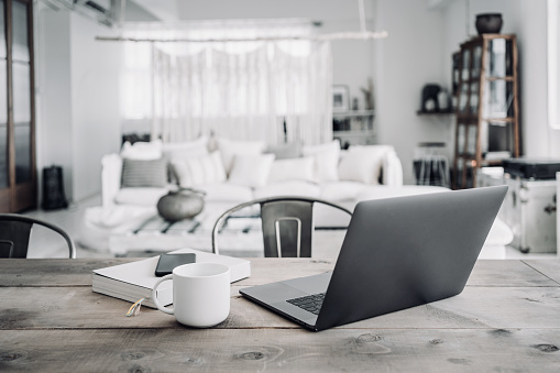 Wireless Technology「A workspace at loft apartment with a laptop, a coffee cup, a book and smartphone in the living room」:スマホ壁紙(12)