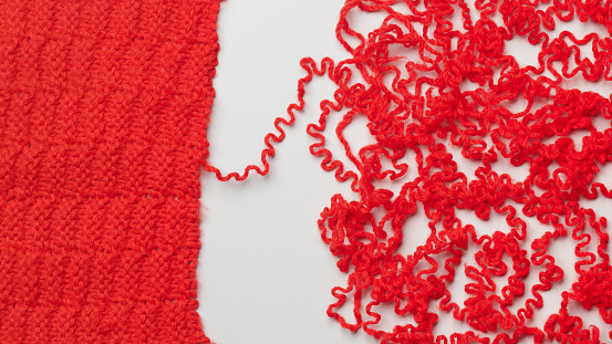Destruction「Knitted red wool unraveling on a white background.」:スマホ壁紙(11)