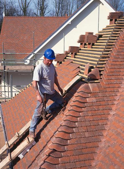 Construction Equipment「Roof tiler fixing hip bonnet tiles to roof of detached house.」:写真・画像(16)[壁紙.com]