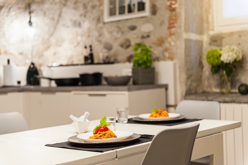 Dining Table「Modern kitchen in old stone house with freshly cooked pasta on table」:スマホ壁紙(11)