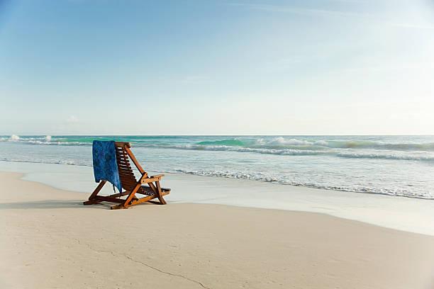 Deck chair on sandy beach at water's edge:スマホ壁紙(壁紙.com)
