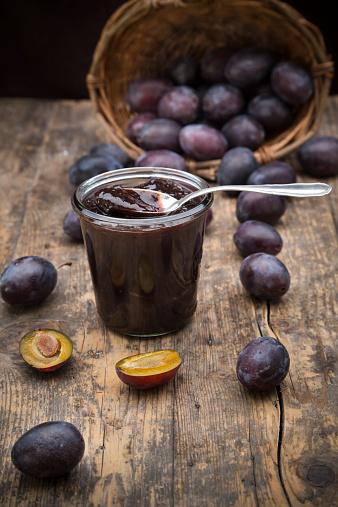 スモモ「Preserving jar of plum jam and plums on wooden table」:スマホ壁紙(14)