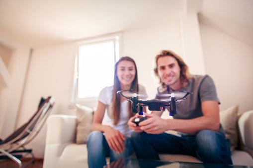 趣味・暮らし「Young couple playing with a small quadrocopter drone」:スマホ壁紙(1)